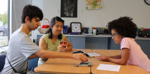 Eric, Xixi, and Sara play Uno at the Hussman Institute.